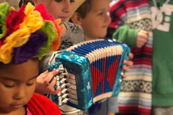 Children in a row playing accordian